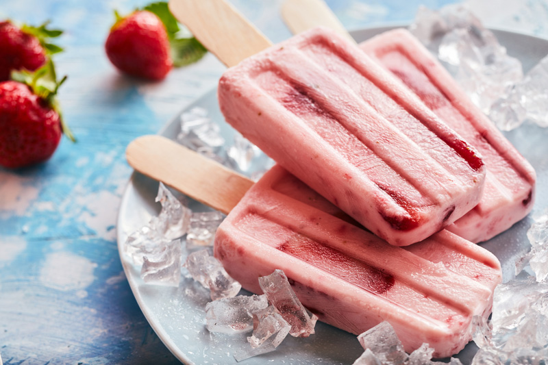 A plate of fresh strawberry coconut popsicles
